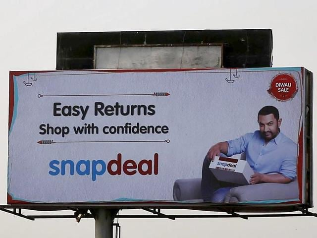 Commuters sit at a bus stop adorned with an advertisement of online marketplace Snapdeal, featuring Bollywood actor Aamir Khan, in Bengaluru.
