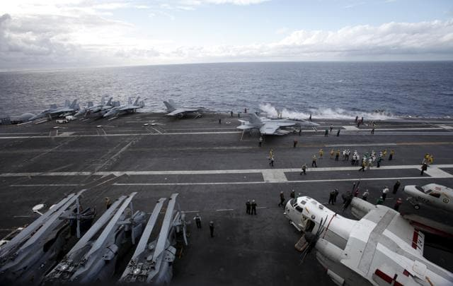 US Navy F/A-18 Super Hornet fighters (top) are seen on the deck of the USS Ronald Reagan, a Nimitz-class nuclear-powered super carrier, in the Pacific Ocean, south of Tokyo, Japan.