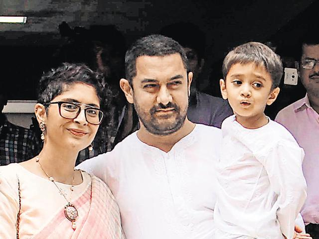 Indian Bollywood actor Aamir Khan, (C), with his wife, director Kiran Rao and son Azad celebrates and wishes his fans Ramzan Eid Mubarak at his residence in Mumbai on July 18, 2015. AFP PHOTO
