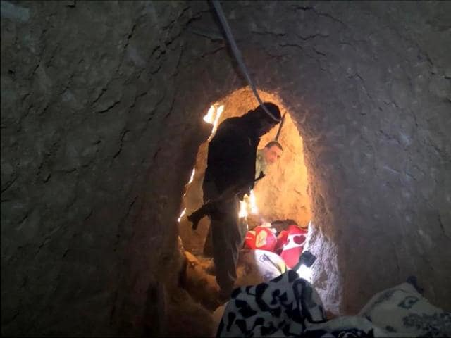 In this image made from video taken on Sunday, Kurdish security forces are seen in a tunnel complex under the city of Sinjar, northern Iraq that were used by Islamic State fighters to move undetected and avoid coalition airstrikes before the town was retaken from the militants.