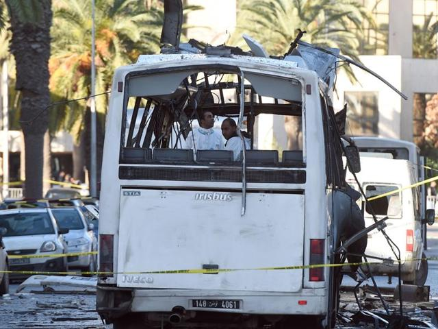 Tunisian forensic police inspect the wreckage of a bus in the aftermath of a bomb attack on the vehicle which was transporting Tunisia's presidential guard in central Tunis on November 25, 2015.