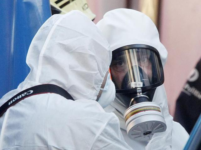 Two men in a white hazmat suits stand near the Grand Mosque of Brussels Thursday. Emergency personnel responded at the mosque after a suspicious package was found.