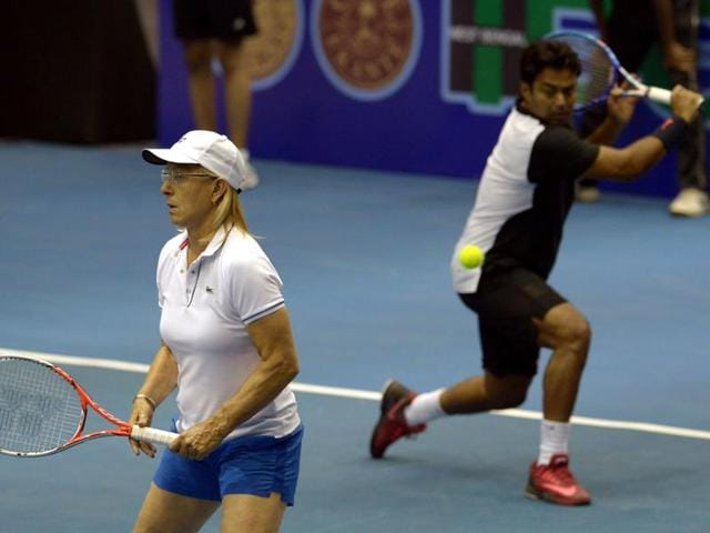 Former US tennis player Martina Navratilova (L) is looks on as tennis player Leander Paes plays a return during an exhibition match of Tennis Masters Kolkata 2015 in Kolkata on November 25, 2015.