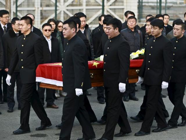 People carry a coffin containing one of the three Chinese victims killed during the attack in Mali.  Two gunmen armed with Kalashnikov assault rifles and explosives stormed the hotel before 7 am on November 20, striking just as security guards were about to change shifts.