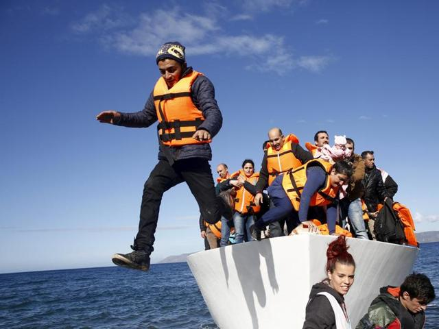 Refugees and migrants jump off a boat as they arrive on the Greek island of Lesbos.