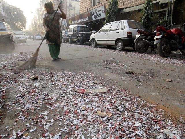 MCD workers clean a street littered with burst crackers on the morning after Diwali in Patel Nagar, New Delhi.