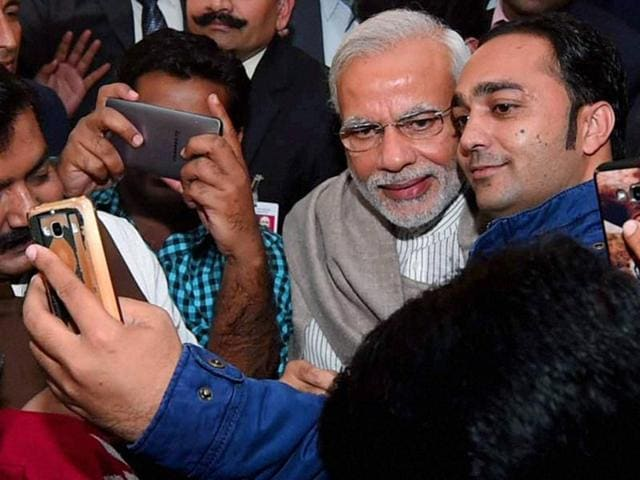 Prime Minister Narendra Modi poses for selfies with journalists during the Diwali Mangal Milan at BJP headquarters in New Delhi on Saturday.