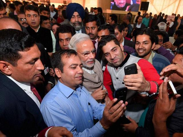 Prime Minister Narendra Modi poses for a selfie with reporters during the Diwali Mangal Milan at BJP headquarters in New Delhi on Saturday.