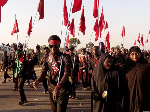 Shia Muslims march on the highway during a symbolic procession commemorating the 40th anniversary of the Ashura religious ceremony on November 27, 2015 in the village of Dakasoye, northern Nigeria, following a suicide bombing attack.