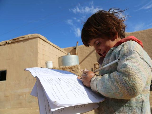 Four-year-old Syrian girl, Baydaa, scribbles on a leaflet of religious rules left behind by the Islamic State (IS) group as they fled, in the Al-Shallal suburb of the northeastern town of Al-Hol in Syria's Hasakeh province, bordering with Iraq.