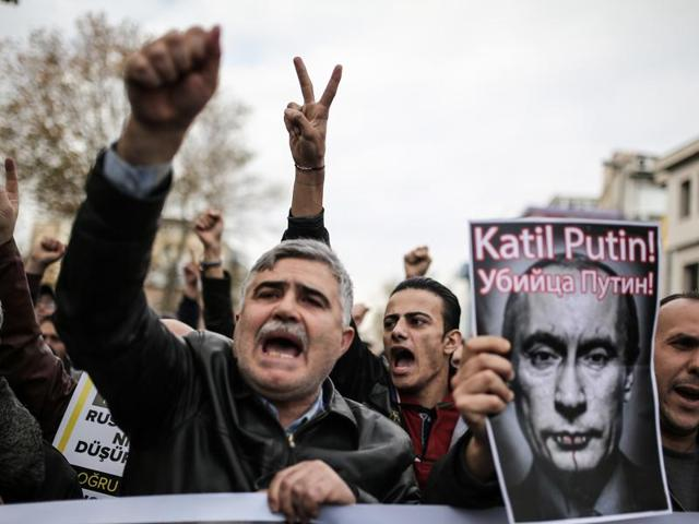 Protesters shout slogans and hold a poster depicting Russian President Vladimir Putin and reading