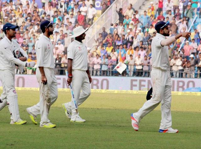 India's Ravichandran Ashwin (L) celebrates with teammates after taking the wicket of South Africa's Dane Vilas during the third day of their third test cricket match in Nagpur on November 27, 2015.