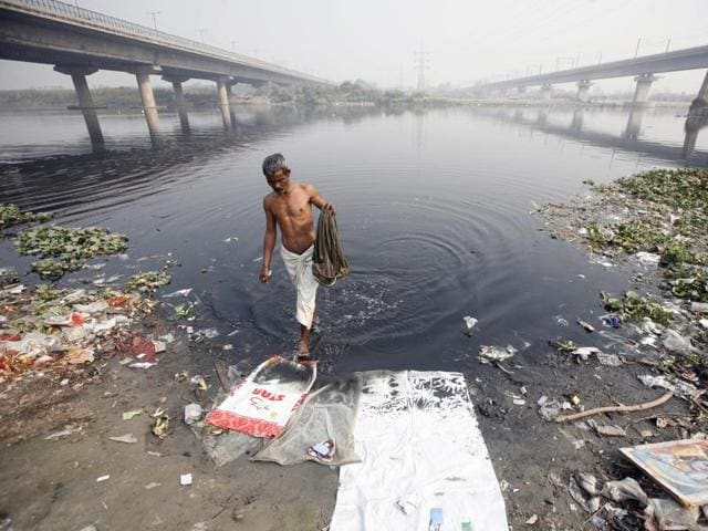 A man takes a bath in the polluted waters of river Yamuna on a winter morning in New Delhi.