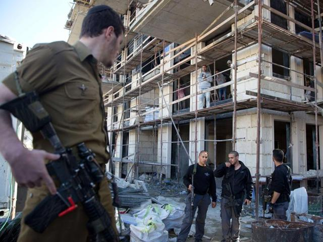 Israeli policemen search for a Palestinian man, who is suspected of stabbing and wounding a woman in north Jerusalem earlier in the day, in a neighborhood in the centre of Jerusalem, on November 29, 2015.