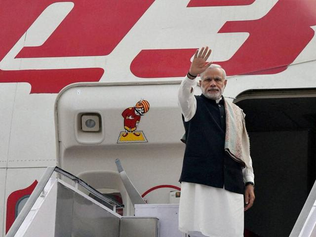 Prime Minister Narendra Modi waves before his departure for France to attend the Paris Climate Conference, at AFS Palam in New Delhi on Saturday.