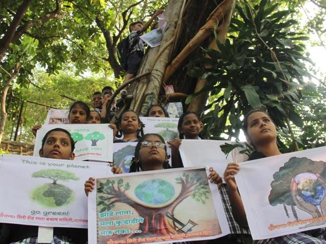 Schoolchildren hug trees in the Kamala Nehru park and hold up placards in a silent protest with citizens on Sunday.