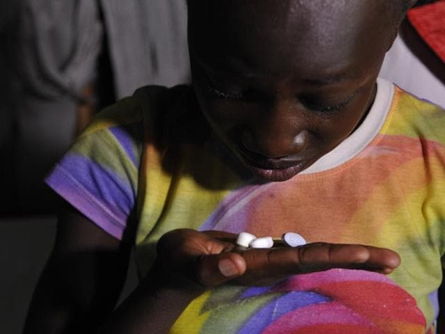 A 13-year-old girl living with AIDS and who lost both parents to the disease, taking her drugs at her grandmothers house in Kenya.
