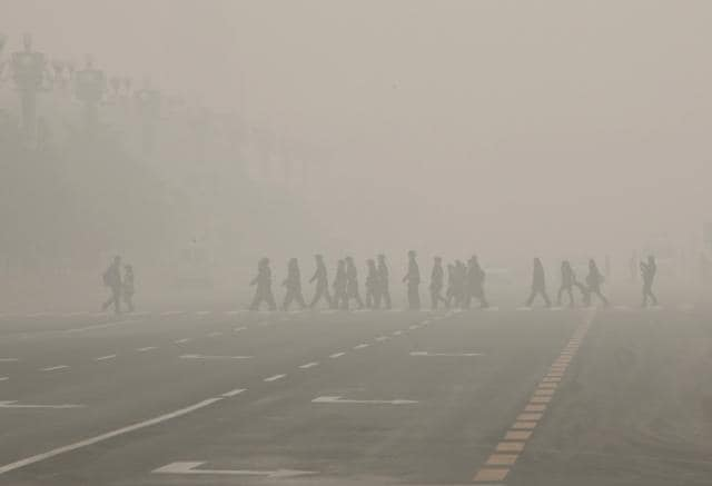 Pedestrians and policeman cross the street at the Tiananmen Square during a heavily polluted day in Beijing, China. Both New Delhi and Beijing were enveloped in smog even as Paris climate summit begins on Monday.