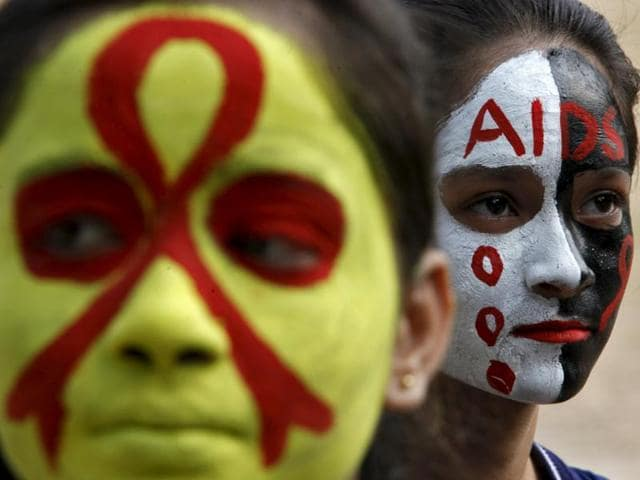 Students wait for their face paint to dry before an AIDS awareness rally inside a school on the eve of World AIDS Day, in Chandigarh.