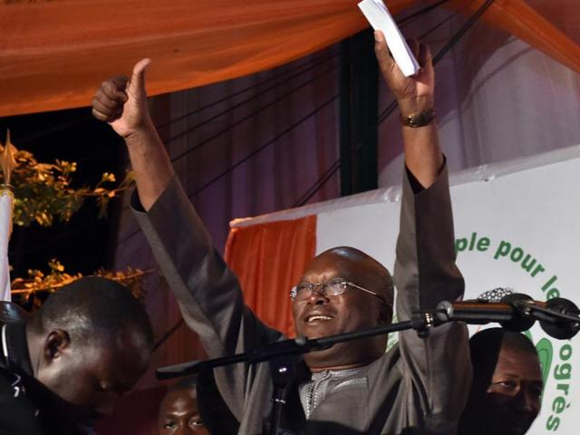 Roch Marc Christian Kabore waves to supporters at party headquarters in Ouagadougou on December 1, 2015 after winning Burkina Faso's presidential election.