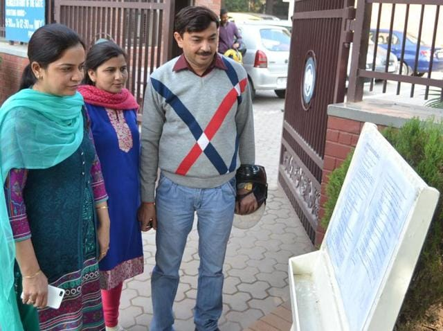 Parents reading details of the admission process at Government Model School, Sector 10, Chandigarh on Monday.