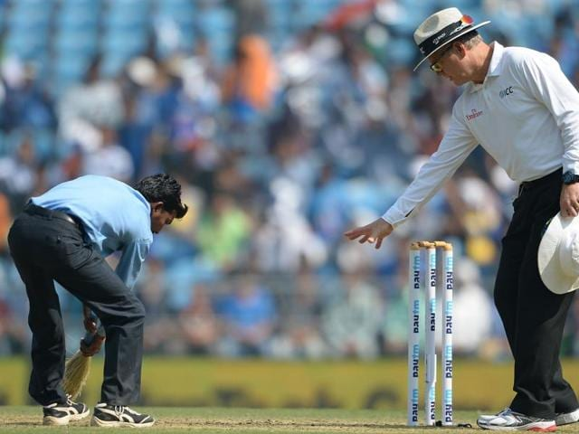 Umpire Bruce Oxenford (R) instructs a member of the groundstaff to sweep dust off the pitch during play on the first day of the third Test cricket match between India and South Africa at The Vidarbha Cricket Association Stadium in Nagpur.