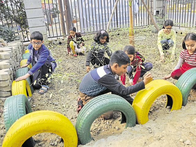 Children are using tyres instead of flower pots to grow plants in the garden at the Shipra Krishna Vista Apartments.