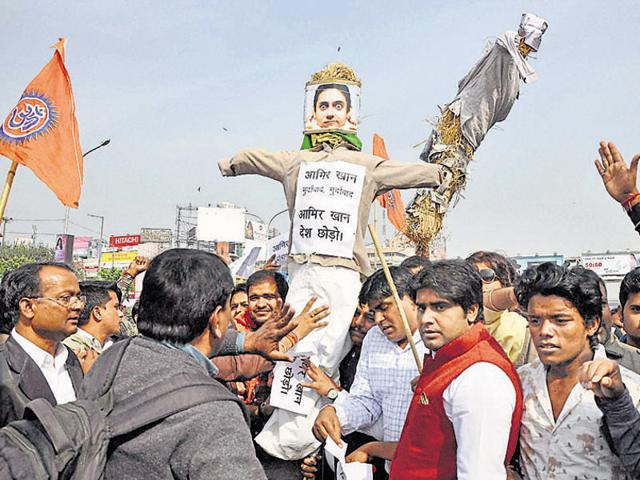 BJP activists burn a poster of Bollywood actor Aamir Khan as they protest over actor's intolerance remark, in Patna, Bihar, India on Tuesday, November 24, 2015.
