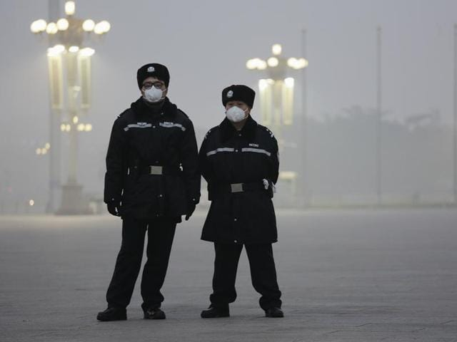 A pedestrian walks on a bridge on an extremely polluted day as hazardous, choking smog continues to blanket Beijing.