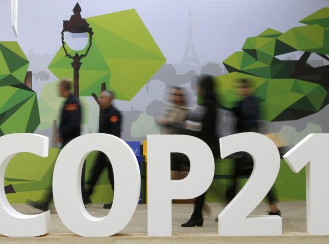 People walk past the COP21 logo in the Climate Generations area during the World Climate Change Conference 2015 (COP21) at Le Bourget, near Paris.