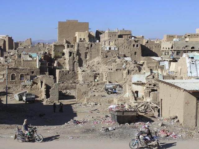 People ride motorcycles past houses damaged during recent conflict in Yemen's northwestern city of Saada December 1, 2015.