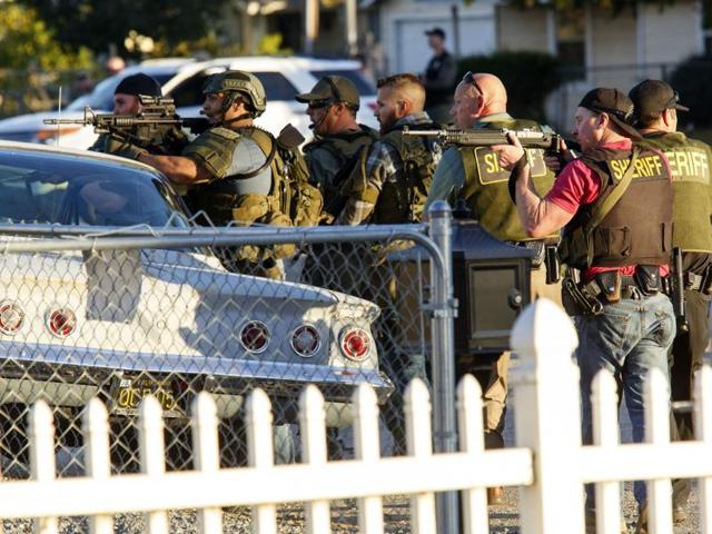 Law enforcement officers search for the suspects of a mass shooting in San Bernardino, California. A man and a woman suspected of carrying out a deadly shooting at a center for the disabled were killed in a shootout with police, while a third person was detained, police said.