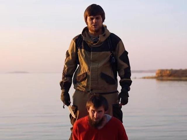 This image made from video released by Islamic State militants, shows a man who identified himself as Magomed Khasayev of Chechnya, bound and kneeling in front of another Russian-speaking man with a knife.