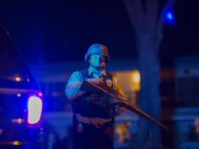 A cop guards a police line as officers prepare to raid the home of a suspect of a mass shooting at the Inland Regional Center in San Bernardino, California.