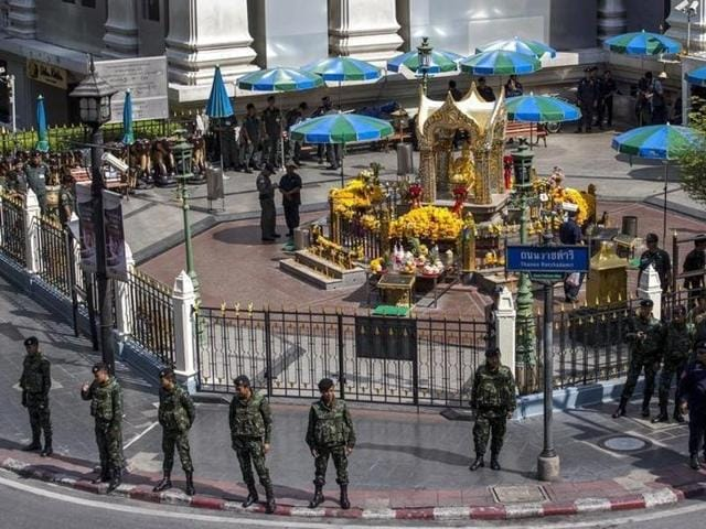 Military personnel and police officers stand guard before a crime re-enactment near the bomb site at Erawan Shrine in Bangkok, Thailand.