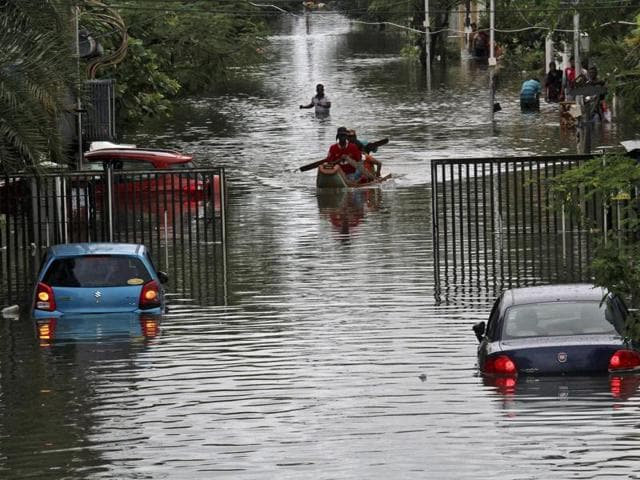 Chennai: A man takes his belongings and moves to safety from the flooded Kotturpuram region of Chennai on December 2, 2015.