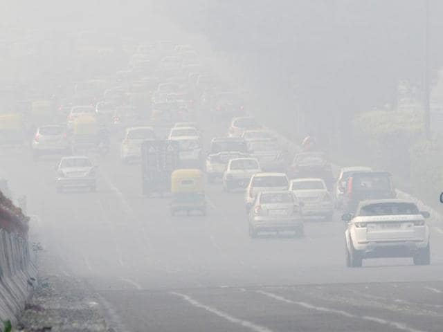 Citizens cover their faces while going out on a smoggy morning, in New Delhi.