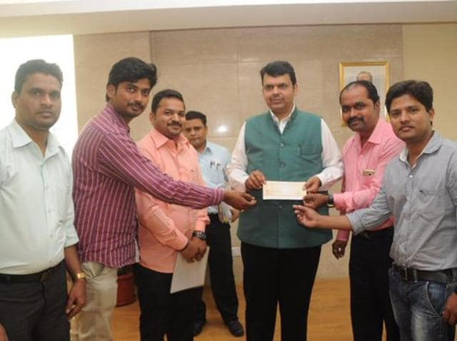 CM Devendra Fadnavis (C) meets with Mangesh Ahiwale (R) ,  a vada pav seller in Mumbai who donated Rs 20,000 to the Chief Minister's Relief Fund.