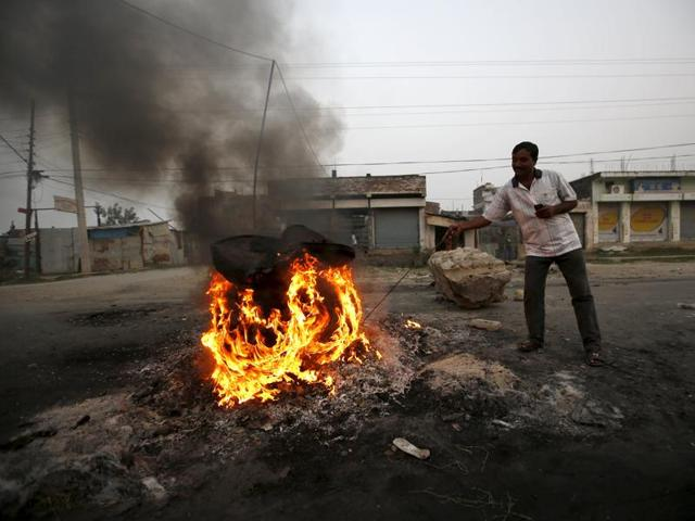 A protester burns a tyre on the highway connecting Nepal to India during a general strike called by the Madhesi protesters demonstrating against the new constitution in Birgunj.