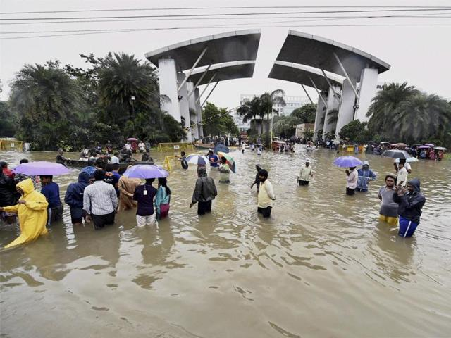Chennai: People wade through waterlogged road at Porur in Chennai. The state of Tamil Nadu is grappling with  heaviest rains it has seen in a  100 years.