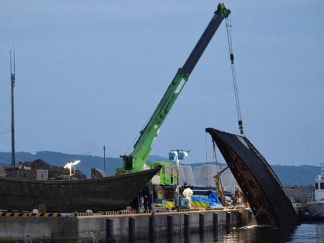 This picture taken on November 21, 2015 shows a wooden boat being salvaged at a port in Wajima in Ishikawa prefecture, central Japan.
