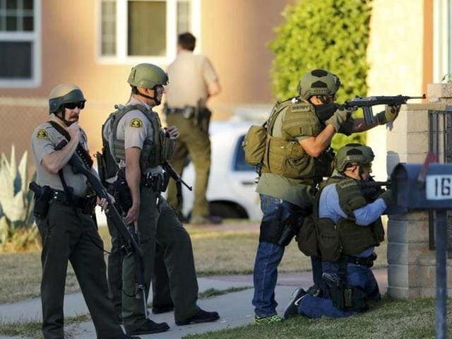 Police officers conduct a manhunt after the shooting rampage in San Bernardino, California.