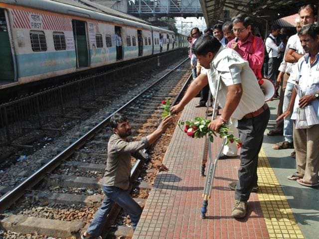 A rose is given to a person who was crossing tracks at Thane station, during an awareness drive organised by Thane Pravasi Sanghatana on the occasion of World Disability Day on Thursday.