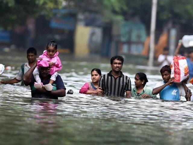 People wade through flood waters in rain-hit Chennai.