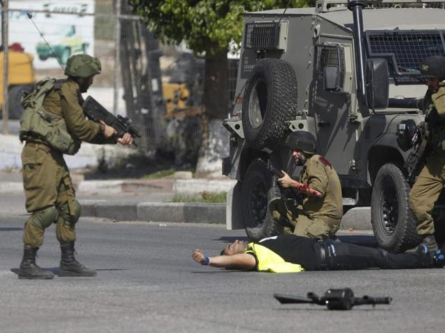 An Israeli soldier shoots a Palestinian holding a knife after he stabbed another Israeli soldier, seen kneeling, during clashes in Hebron.