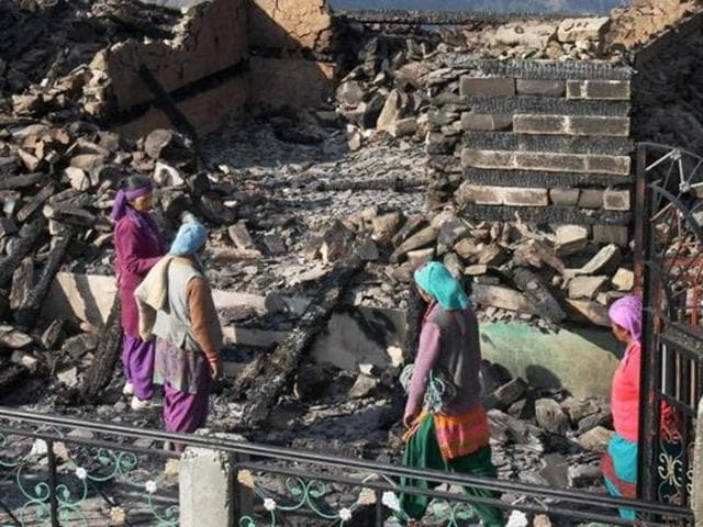Women sifting through what is left of their homes after the fire on November 15 night destroyed as many as 72 houses in the village.