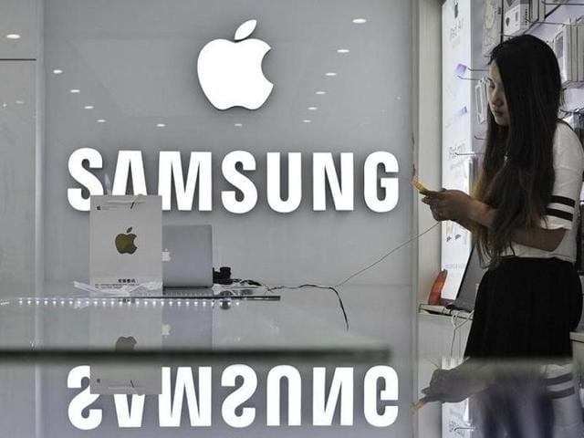 A sales assistant uses her mobile phone next to the company logos of Apple and Samsung at a store.