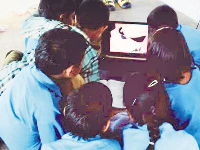 Students watch an educational video in a classroom at a government school.