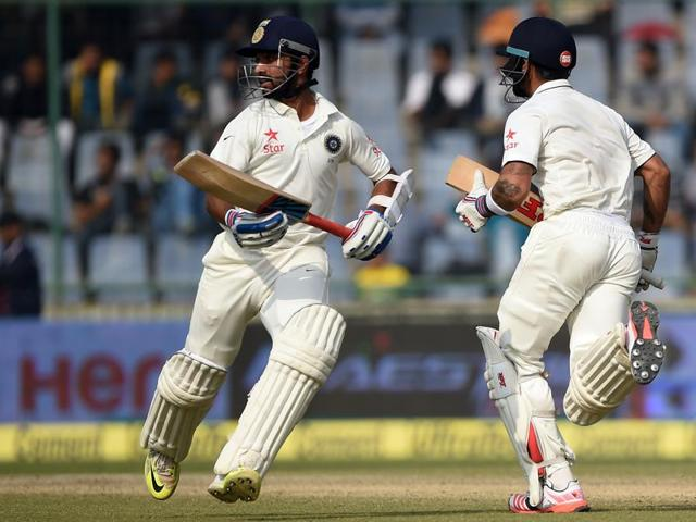 India's captain Virat Kohli, center and batsman Ajinkya Rahane, left run between the wickets as South Africa's bowler Kyle Abbott, right watches on the third day of the fourth test cricket match between India and South Africa in New Delhi.