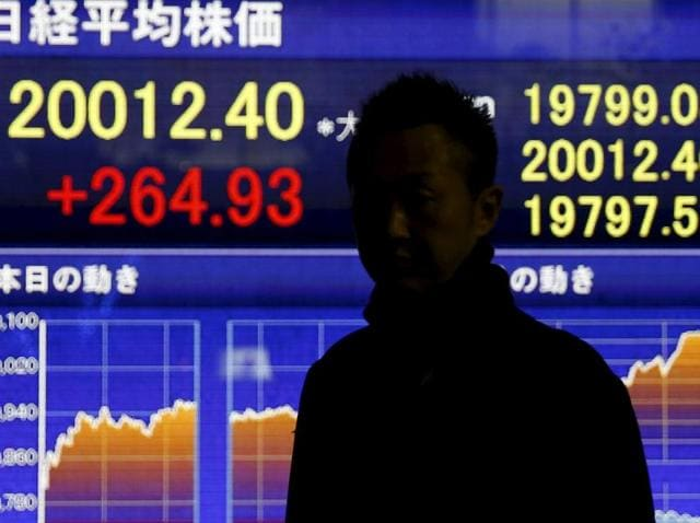 """A man stands in front of an electronic board showing Japan's Nikkei average outside a brokerage in Tokyo. The Bank for International Settlements (BIS) issued a warning Sunday over an """"uneasy calm"""" within financial markets, noting that the global economy remains vulnerable to serious disruptions."""